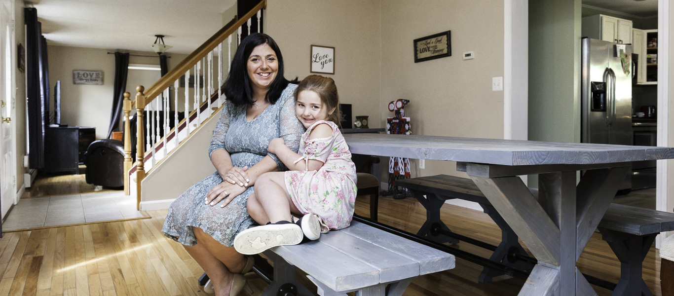 Mother and Daughter sitting on a bench in their home
